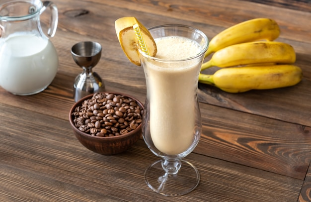 Copo de cocktail de banana sujo com ingredientes em superfície de madeira