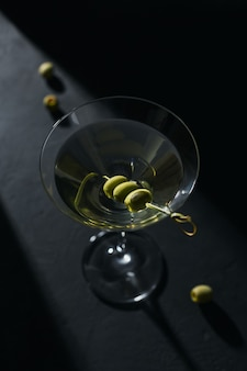 Copo de cocktail de martini seco clássico com azeitonas na mesa de pedra escura contra um negro.