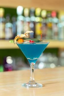 Copo de cocktail decorado com frutas no balcão de bar.