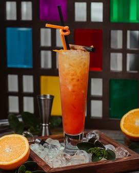 Copo de cocktail laranja com cachimbo e cubos de gelo picado