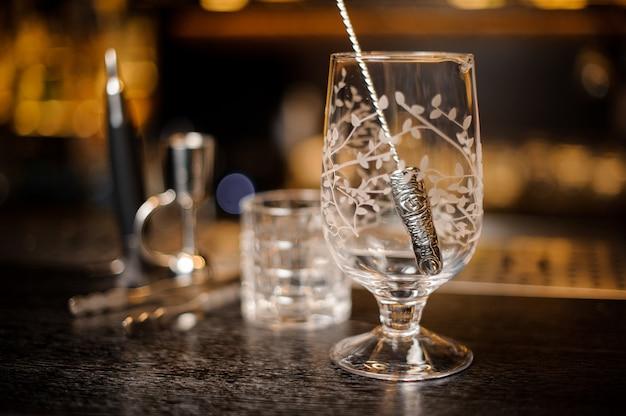 Copo de cocktail vazio com uma colher no balcão do bar
