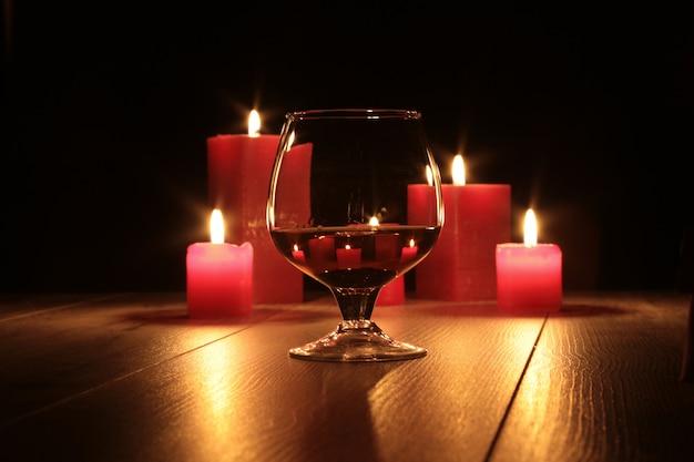 Copo de conhaque e vela vermelha em uma madeira
