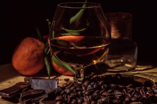 Copo de conhaque na mesa de madeira com chocolate, café e tangerinas.