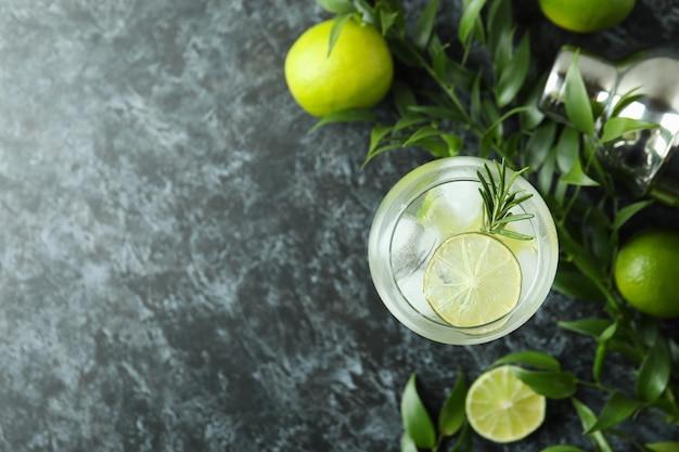 Copo de coquetel com limão na mesa esfumada preta