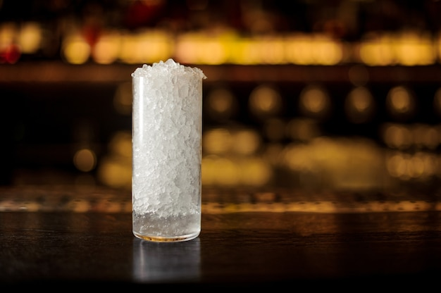 Copo de coquetel com pedaços de gelo no balcão do bar ao fundo das luzes douradas do restaurante