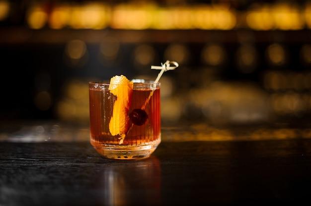 Copo de coquetel com whisky decorado com casca de laranja e cereja no balcão do bar