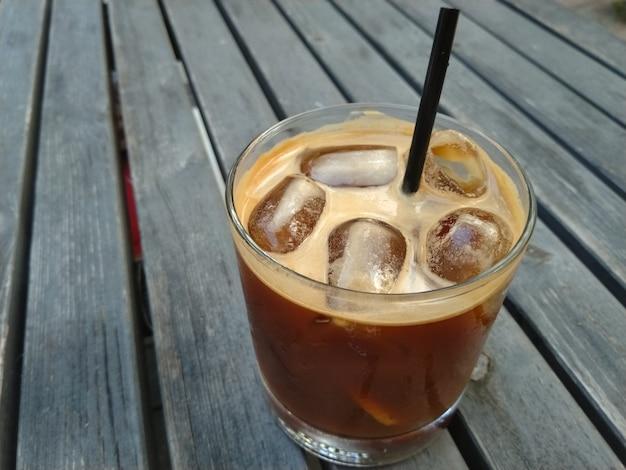 Copo de coquetel de café com tônica e gelo na mesa de madeira