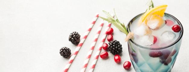 Copo de coquetel de frutas com ângulo alto com espaço de cópia e canudos