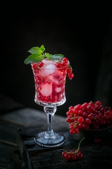 Copo de coquetel de groselha ou mocktail, bebida refrescante de verão com gelo picado e água com gás