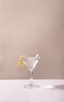 Copo de coquetel de martini com gota de limão na mesa contra um fundo cinza