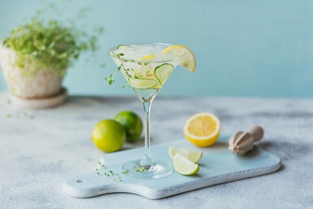 Copo de coquetel de pepino ou mocktail, bebida refrescante de verão com gelo picado e água com gás em uma madeira
