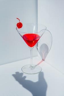 Copo de coquetel e cereja vermelha com sombra de mão em um canto branco. luz natural