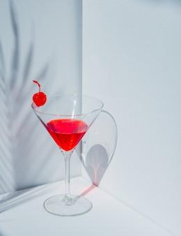 Copo de coquetel e cereja vermelha em um canto branco. luz natural