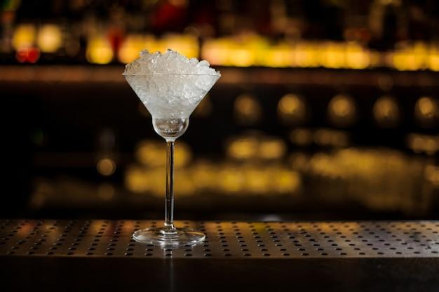 Copo de coquetel elegante cheio de pedaços de gelo no balcão do bar contra as luzes