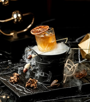 Copo de coquetel frio, decorado com uma fatia de laranja seca, servido no balde defumado