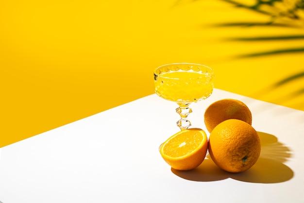 Copo de coquetel ou suco de laranja sob a sombra de uma palmeira e do sol.