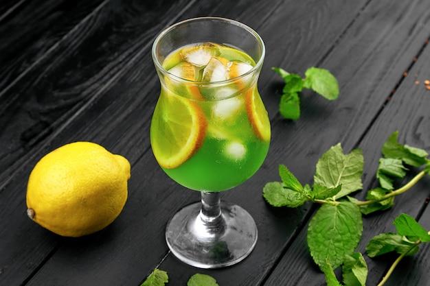 Copo de coquetel verde frio com limão e hortelã. mojito. limonada de frescura de verão com gelo. fundo escuro. copie o espaço.