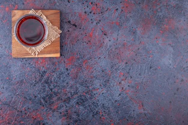 Copo de coquetel vermelho com fatias de frutas em mármore.