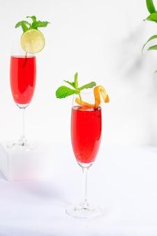 Copo de coquetel vermelho feito de vodka e vinho espumante no fundo branco