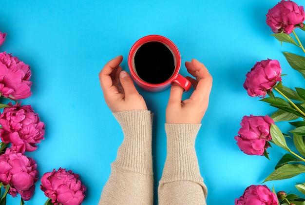 Copo de creameric vermelho com café preto nas mãos femininas e um buquê de peônias vermelhas