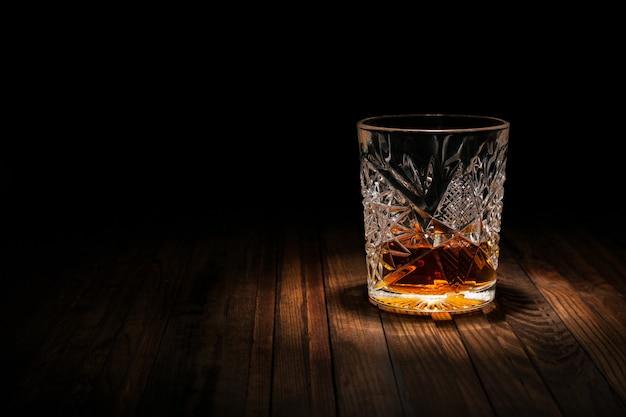 Copo de cristal com uísque e lanches em uma mesa de madeira em um fundo preto