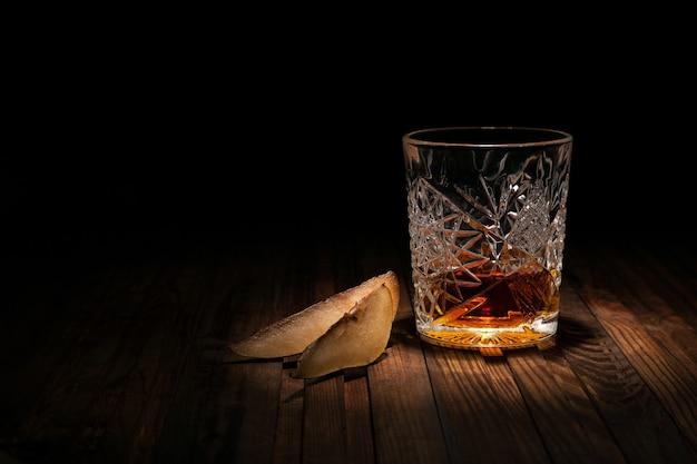 Copo de cristal de uísque em uma mesa de madeira em preto