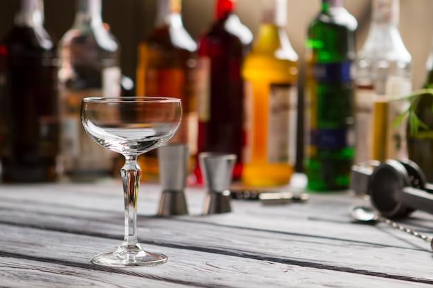 Copo de cupê vazio. vidro na superfície de madeira cinza. relaxe no bar local. muitos tipos de álcool.