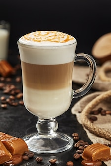 Copo de delicioso latte macchiato com calda de caramelo