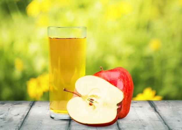 Copo de delicioso suco de maçã e maçãs frescas