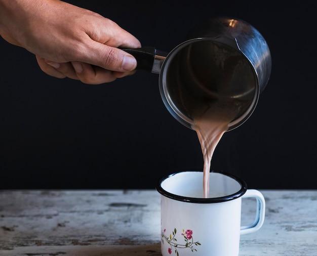 Copo de enchimento de mão de colheita com chocolate quente