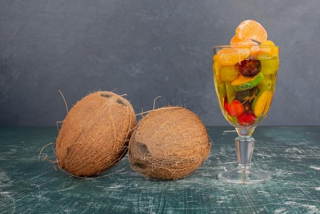 Copo de frutas e cocos na mesa de mármore
