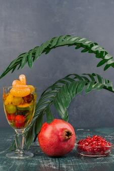 Copo de frutas e romã com sementes na mesa de mármore