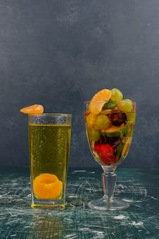 Copo de frutas e suco de tangerina na mesa de mármore