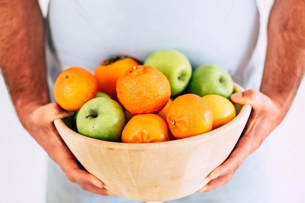 Copo de frutas frescas sazonais coloridas, seguradas por um homem com uma grande barriga - conceito de comer saudável e fazer dieta - comida vegetariana e vegana - necessidades de vitaminas e atividades esportivas