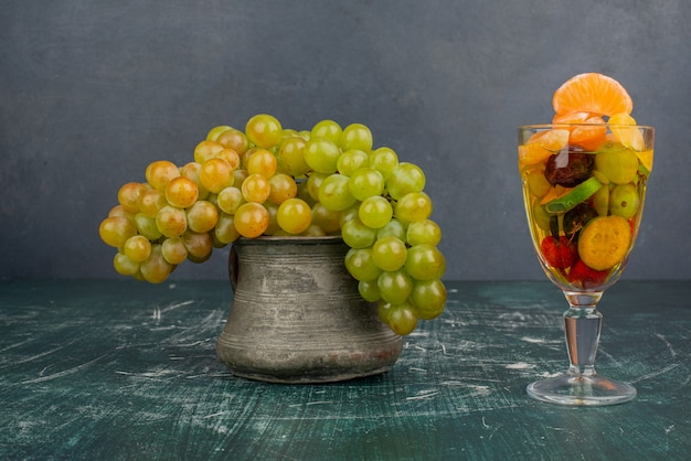 Copo de frutas mistas e cacho de uvas na mesa de mármore.