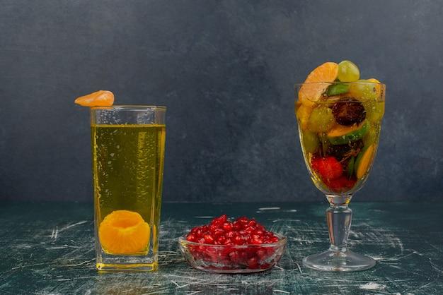 Copo de frutas, suco e sementes de romã na mesa de mármore