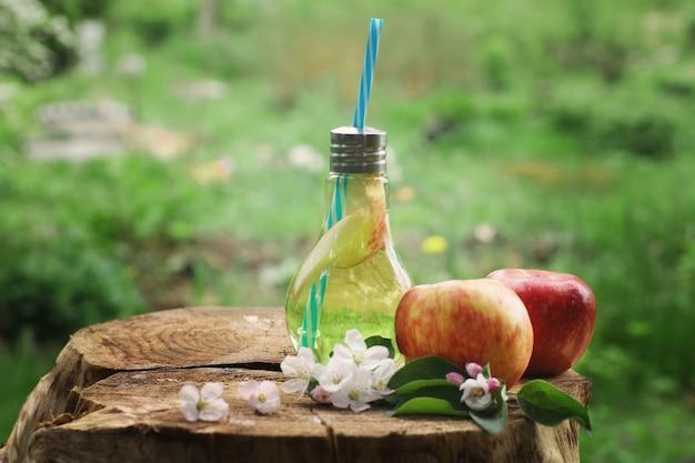 Copo de garrafa com um tubo, cheio de limonada de maçã ao lado de maçãs vermelhas em um toco.