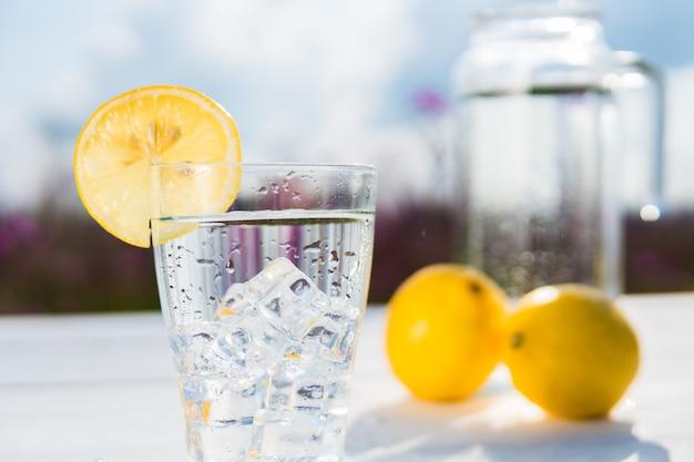 Copo de gelo e água decorado com uma fatia de limão em pé sobre uma mesa branca