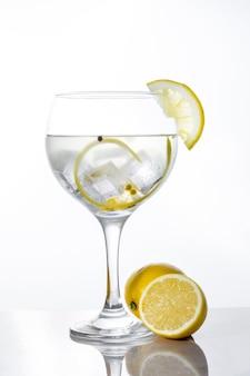 Copo de gin tônico com limão isolado no branco