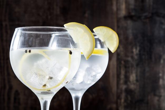 Copo de gin tônico com limão no fundo de madeira