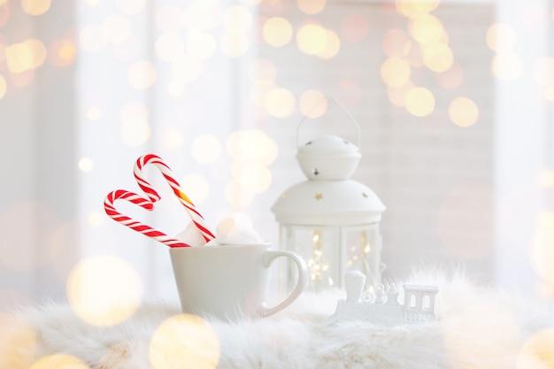 Copo de inverno de bebida quente com um bastão de doces em fundo branco de madeira