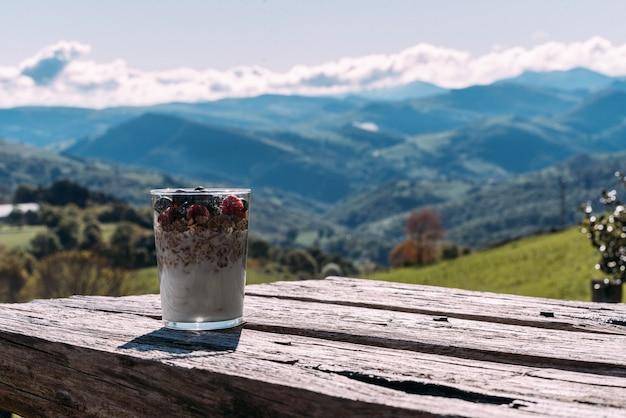 Copo de iogurte caseiro com muesli contra incrível paisagem montanhosa em dia de sol