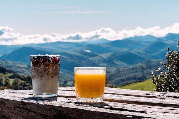 Copo de iogurte caseiro com muesli e framboesas frescas e mirtilos colocado na mesa de madeira contra a incrível paisagem montanhosa em dia ensolarado