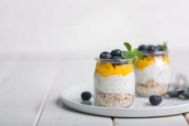 Copo de iogurte com amoras e mousse de manga em um fundo branco