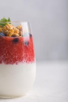 Copo de iogurte com mousse de morango, mirtilos e granola em um fundo branco
