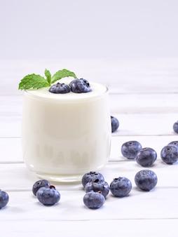 Copo de iogurte de mirtilo na mesa de madeira branca
