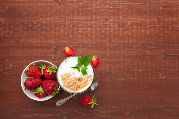 Copo de iogurte de morango saudável com frutas frescas na vista superior de mesa de madeira