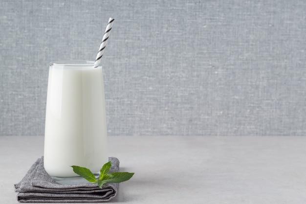 Copo de iogurte kefir ou ayran na mesa cinza espaço vazio leite natural fermentado