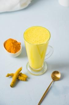 Copo de leite açafrão dourado, curcuma em pó. fechar-se.
