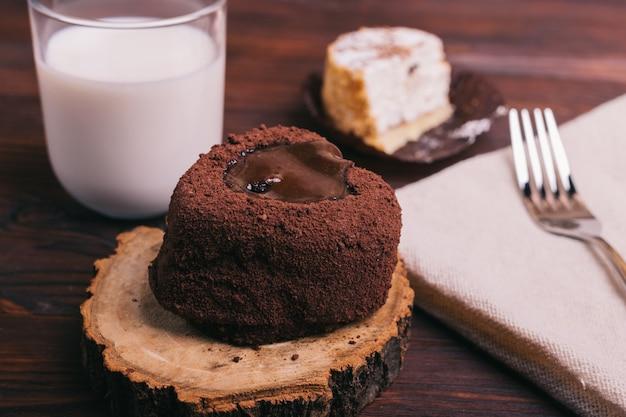 Copo de leite, bolos e garfo na mesa marrom